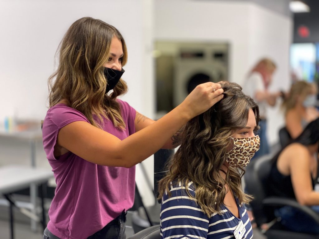 A student hairdresser touches a client's hair while wearing a mask. She is adhering to COVID-19 Safety Measures.